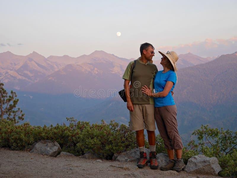 Glückliches Paar, das durch Berge lächelt und umarmt stockfoto