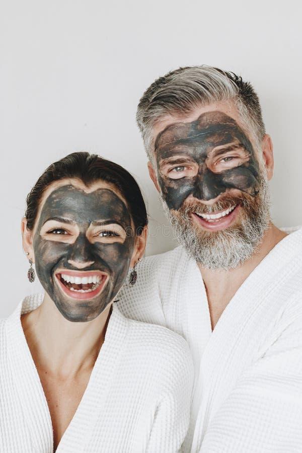 Glückliches Paar, das eine Holzkohlenmaske trägt stockbild