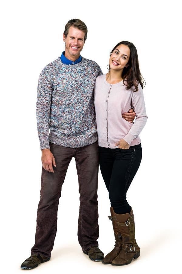 Glückliches Paar, das gegen weißen Hintergrund steht stockbild