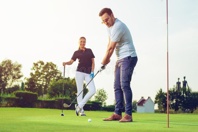 Glückliches Paar, das Golf am Verein spielt stockfotos