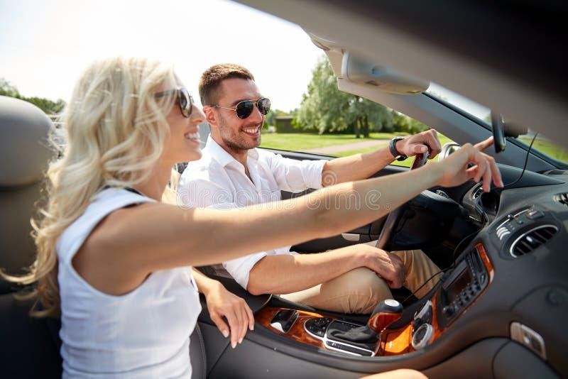 Glückliches Paar, das gps-Navigator im Cabrioletauto verwendet stockfotos