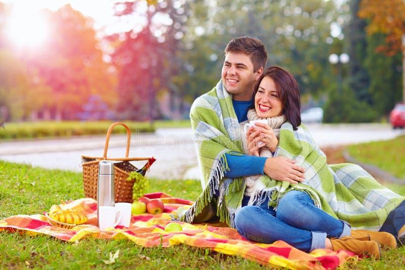 Glückliches Paar, das Herbstpicknick im Stadtpark genießt lizenzfreie stockbilder