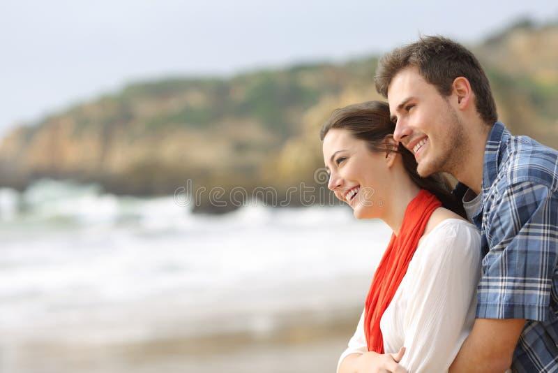Glückliches Paar, das Horizont auf dem Strand umarmt und betrachtet stockbild