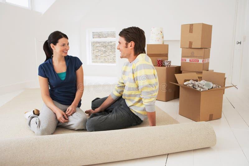 Glückliches Paar, das in ihrem neuen Haus sitzt lizenzfreie stockfotos
