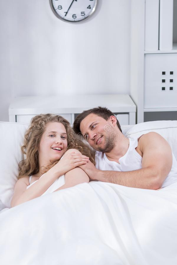 Glückliches Paar, das im Bett liegt stockfotos