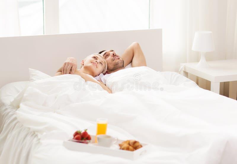 Glückliches Paar, das im Bett mit Behälter des Frühstücks liegt stockbild