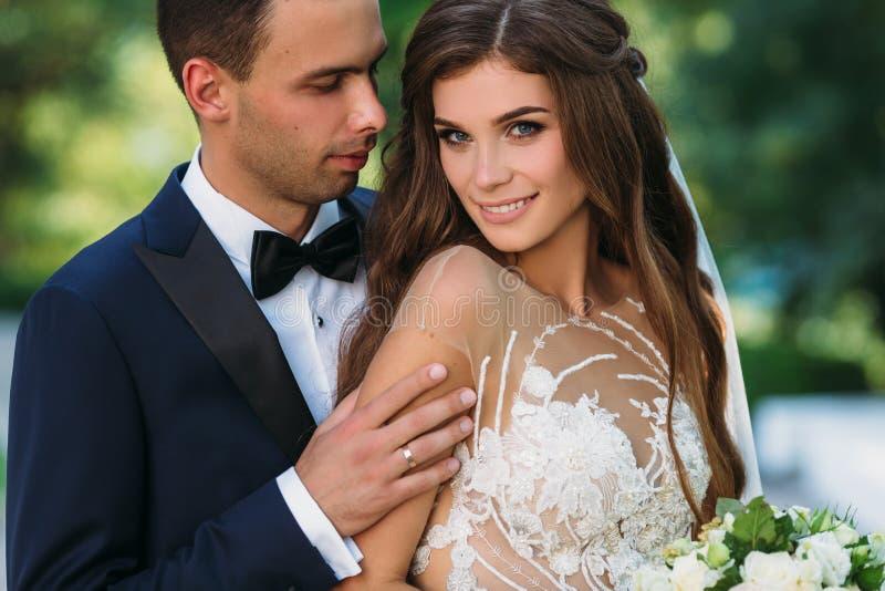 Glückliches Paar, das im Garten mit grünen Bäumen umarmt und lächelt Die Braut in einem schwarzen Anzug mit einer Fliege und eine lizenzfreies stockbild