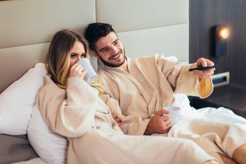 Glückliches Paar, das im Luxushotelraum, aufpassendes Fernsehen frühstückt stockbilder