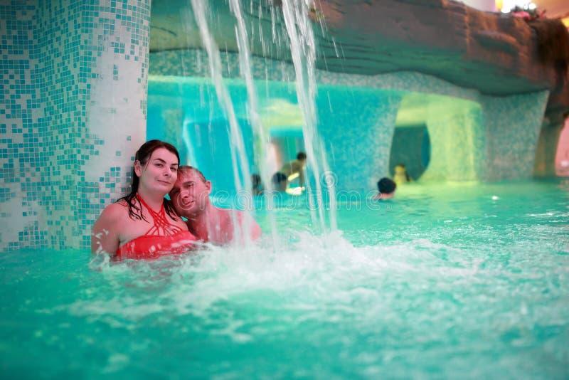 Glückliches Paar, das im Wasserpark umfasst lizenzfreies stockfoto