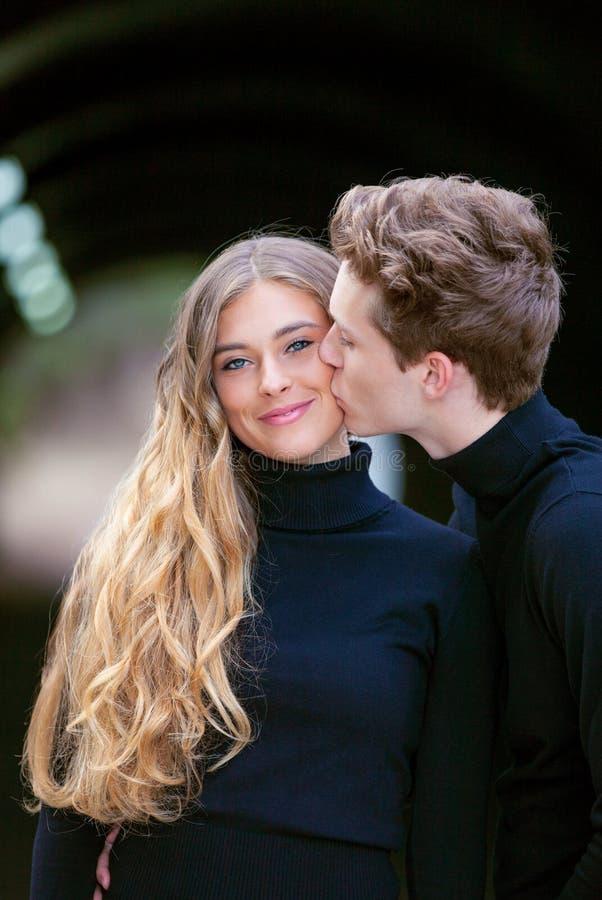 Glückliches Paar, das mit einem Kuss lächelt lizenzfreie stockfotos