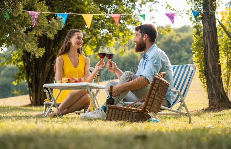 Glückliches Paar, das mit Rotwein beim Feiern ihrer Liebe röstet lizenzfreie stockfotografie