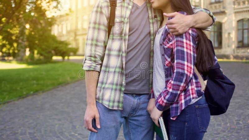 Glückliches Paar, das nahe Universität, Studenten untersuchen viel versprechende Zukunft umarmt lizenzfreies stockfoto