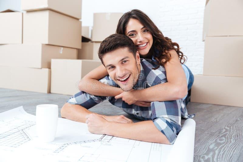Glückliches Paar, das Pläne des neuen Hauses betrachtet lizenzfreies stockfoto