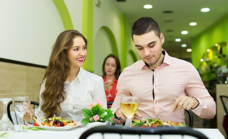 Glückliches Paar, das am Restaurant zu Abend isst stockfoto
