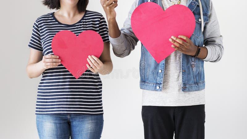 Glückliches Paar, das rote Herzikonen hält stockfotos
