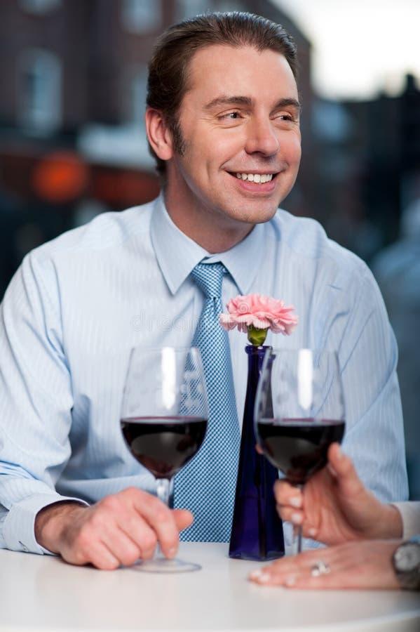 Glückliches Paar, das Rotwein röstet stockfotografie
