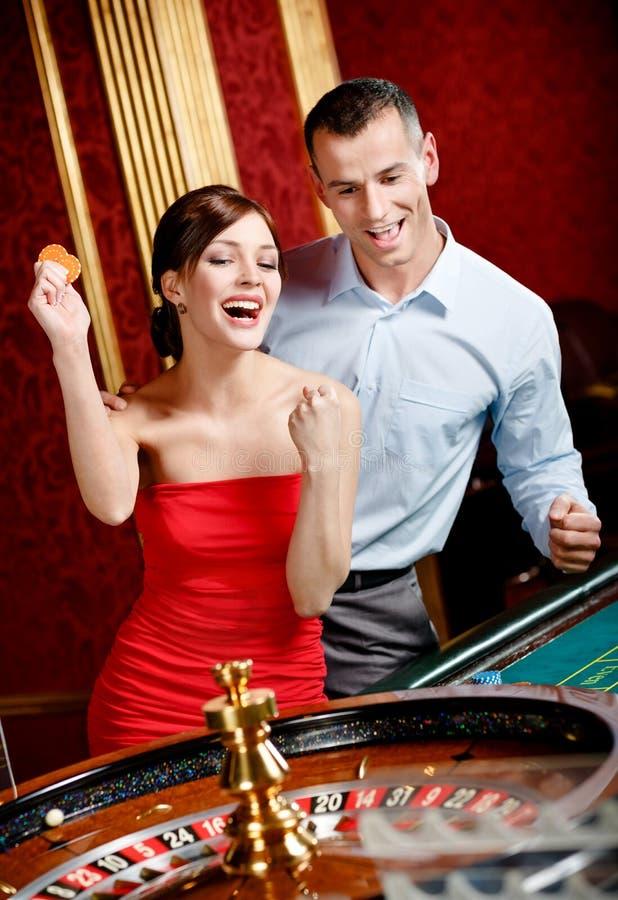 Glückliches Paar, das Roulettegewinne spielt lizenzfreies stockbild