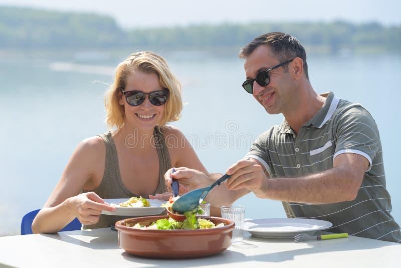 Glückliches Paar, das Salat für Abendessen an der Caféterrasse isst lizenzfreies stockfoto