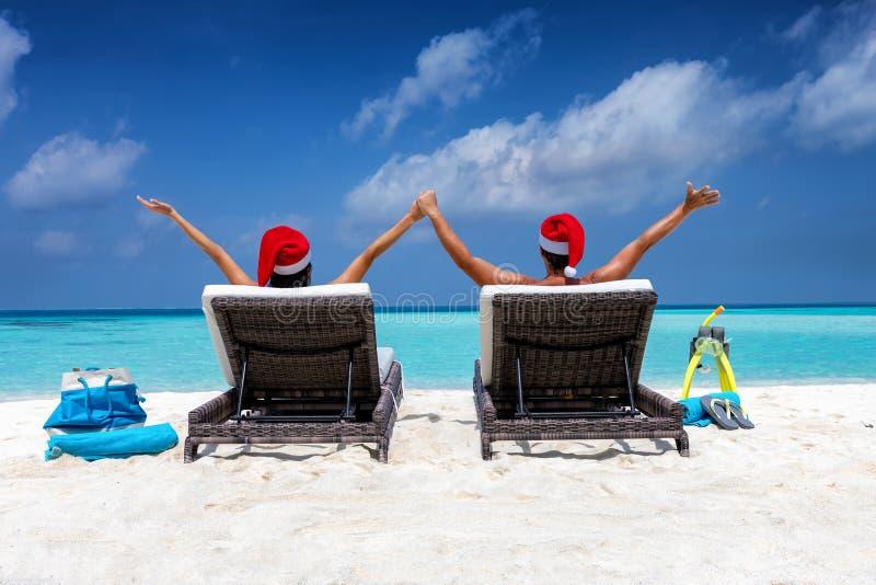 Glückliches Paar, das Sankt-Hüte in den Sonnenstühlen auf einem tropischen Strand während der Weihnachtszeit trägt stockbild