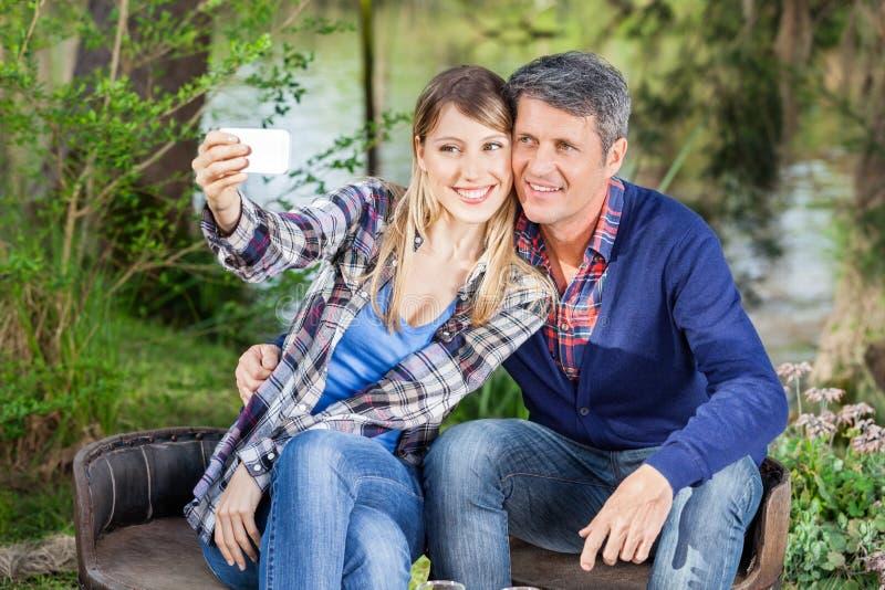 Glückliches Paar, das Selbstporträt am Campingplatz nimmt stockfotografie