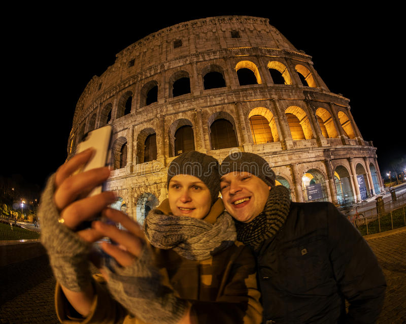 Glückliches Paar, das selfie durch Kolosseum nachts macht lizenzfreie stockfotografie