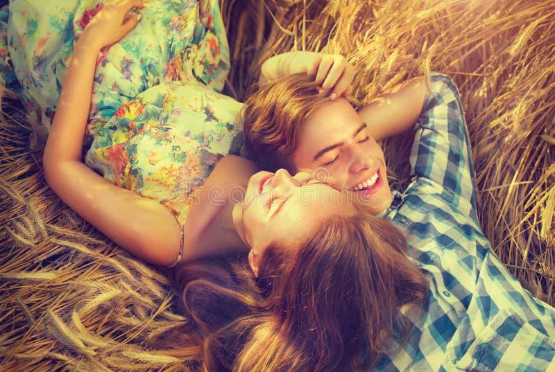 Glückliches Paar, das sich draußen auf Weizenfeld entspannt lizenzfreie stockfotos