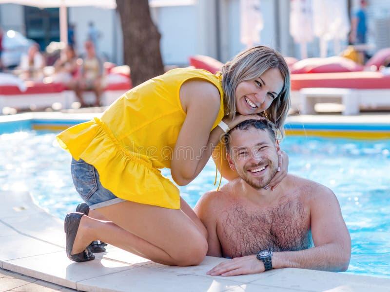 Glückliches Paar, das Sommerzeit n ein FerienzentrumSwimmingpool genießt stockbilder