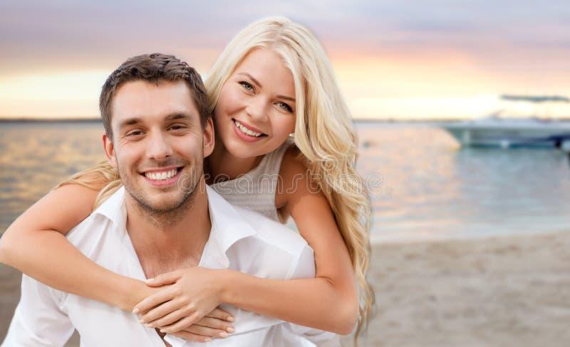 Glückliches Paar, das Spaß über Strandhintergrund hat lizenzfreies stockbild