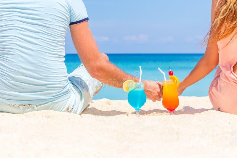 Glückliches Paar, das tropische Cocktails auf Sandstrand genießt stockfoto