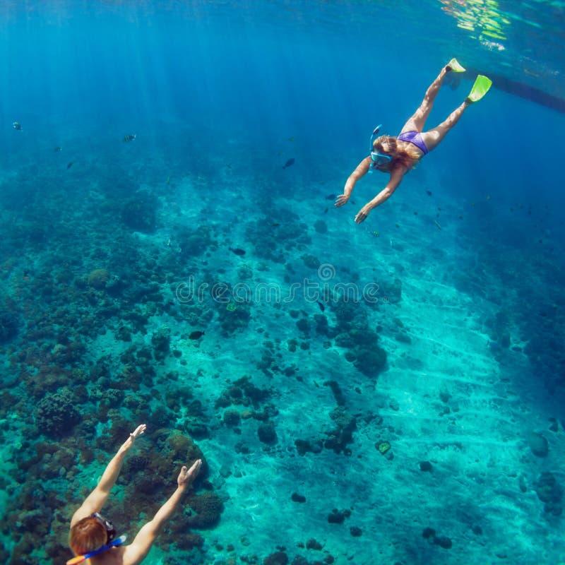 Glückliches Paar, das unter Wasser über Korallenriff schnorchelt stockbild
