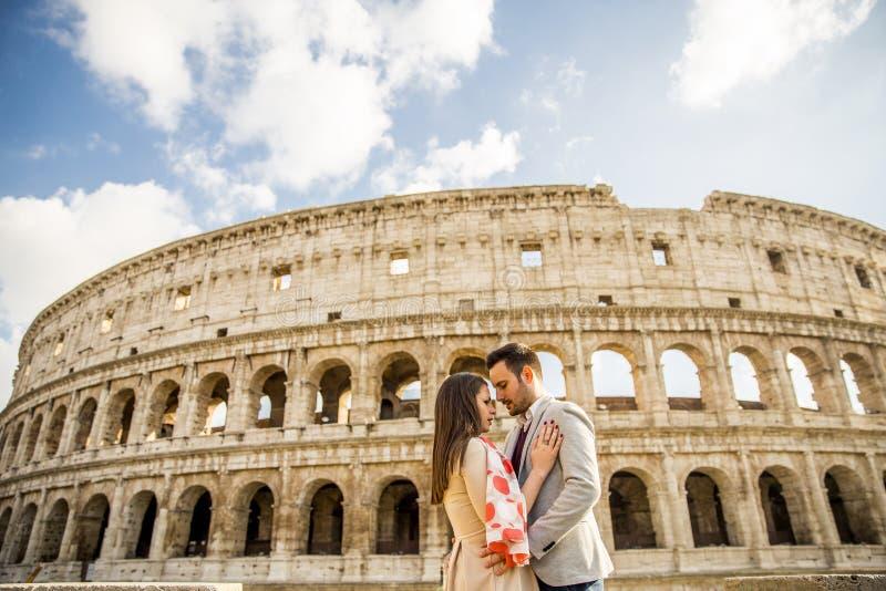 Glückliches Paar, das vor Colosseum in Rom, Italien umarmt lizenzfreies stockbild
