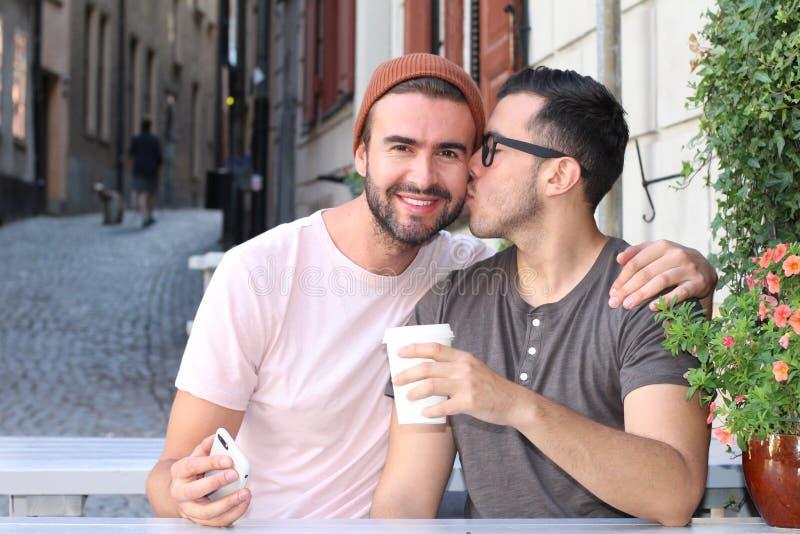 Glückliches Paar, das während des Datums an einem Freiencafé lächelt stockbild