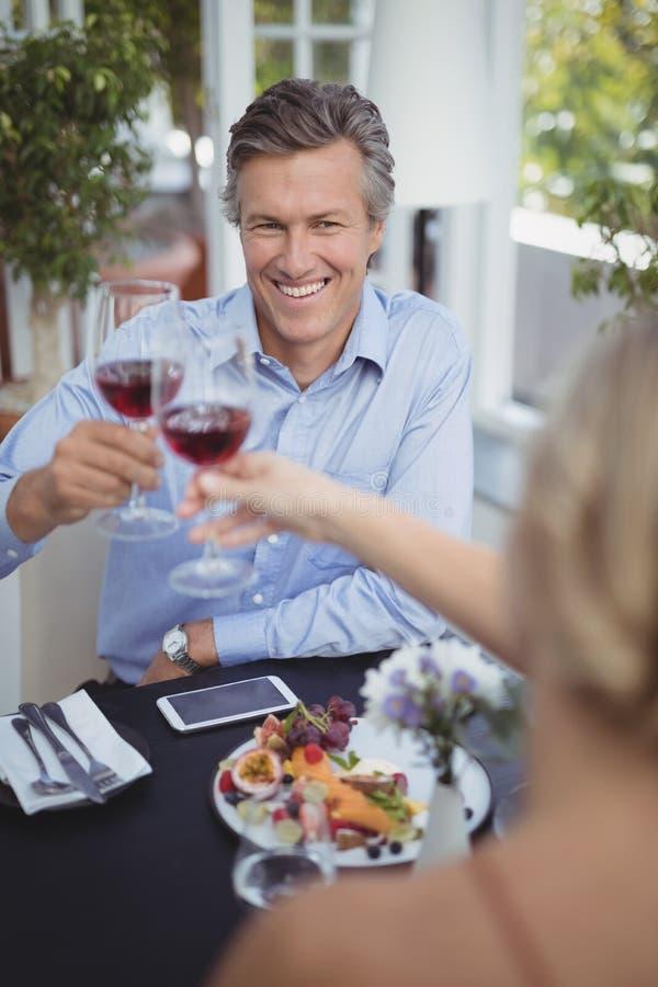 Glückliches Paar, das Weinglas beim Haben der Mahlzeit röstet lizenzfreie stockbilder