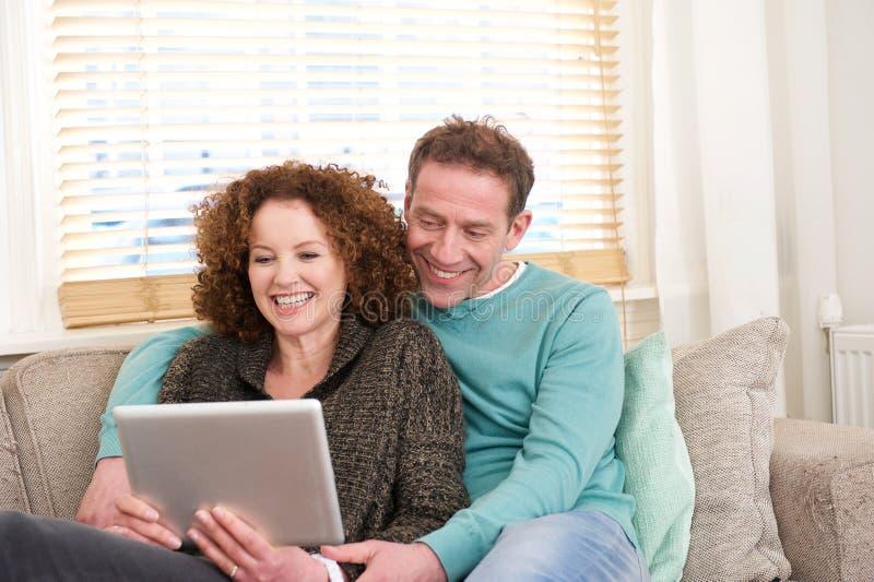 Glückliches Paar, das zu Hause auf dem Sofa betrachtet Computertablette sitzt lizenzfreies stockbild