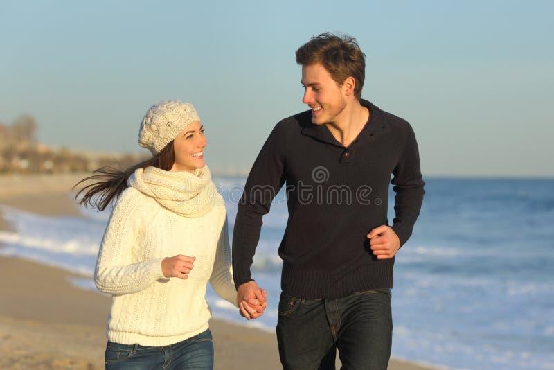 Glückliches Paar, das zusammen auf dem Strand im Winter läuft stockbild