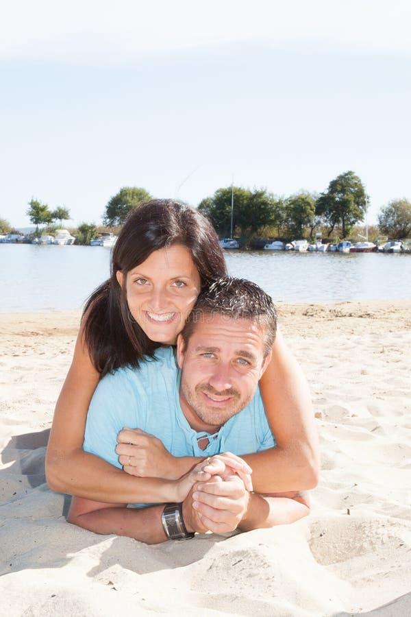 Glückliches Paar, das zusammen auf Sandstrand auf Küste liegt lizenzfreies stockfoto