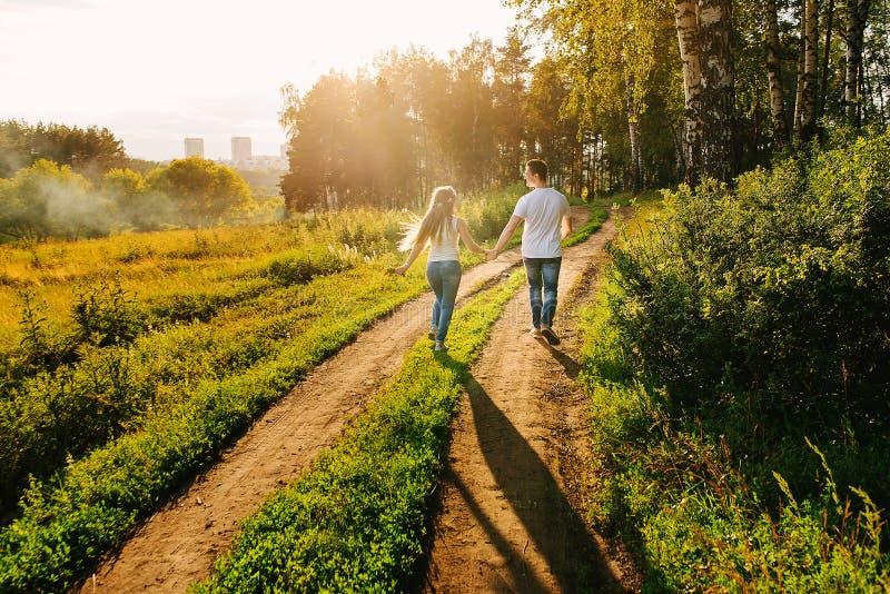 Glückliches Paar, das zusammen in ein Grün geht stockfoto