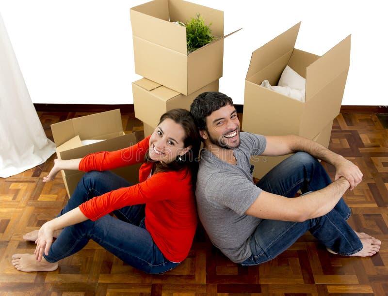 Glückliches Paar, das zusammen in ein neues Haus auspackt Pappschachteln umzieht lizenzfreie stockfotos