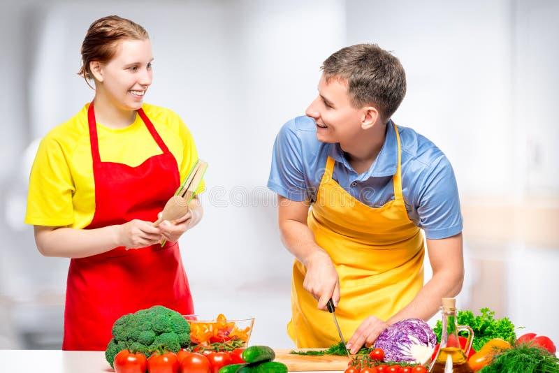 glückliches Paar, das zusammen gesunden und geschmackvollen Gemüsesalat kocht stockfotografie