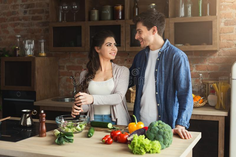Glückliches Paar, das zusammen gesundes Lebensmittel kocht lizenzfreies stockbild