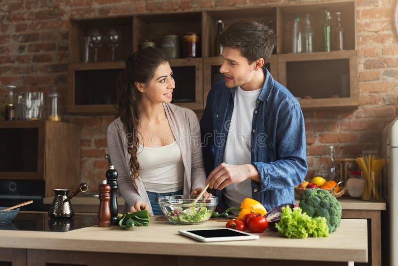 Glückliches Paar, das zusammen gesundes Lebensmittel kocht stockbild