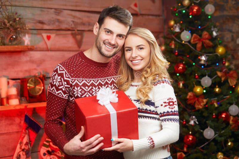 Glückliches Paar in den Winterpullovern lächelnd und große rote Geschenkbox halten stockfotografie