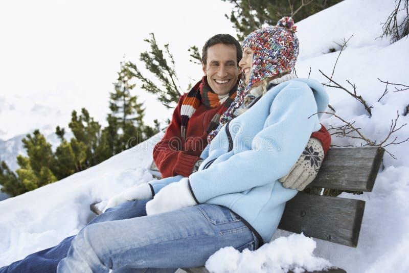 Glückliches Paar in der warmen Kleidung, die auf Bank sitzt lizenzfreies stockbild