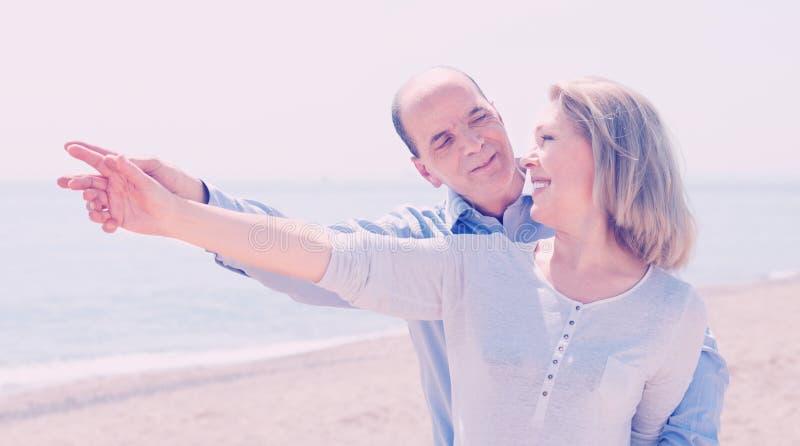 Glückliches Paar in der zufälligen Kleidung Finger zeigend lizenzfreies stockbild