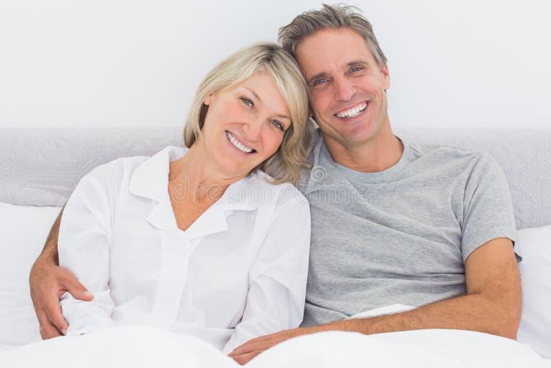 Glückliches Paar im Bett lizenzfreie stockfotos