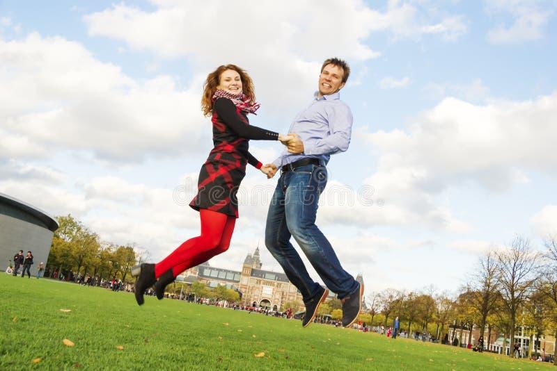 Glückliches Paar im Freien, das in Museumplein, Amsterdam springt stockbilder