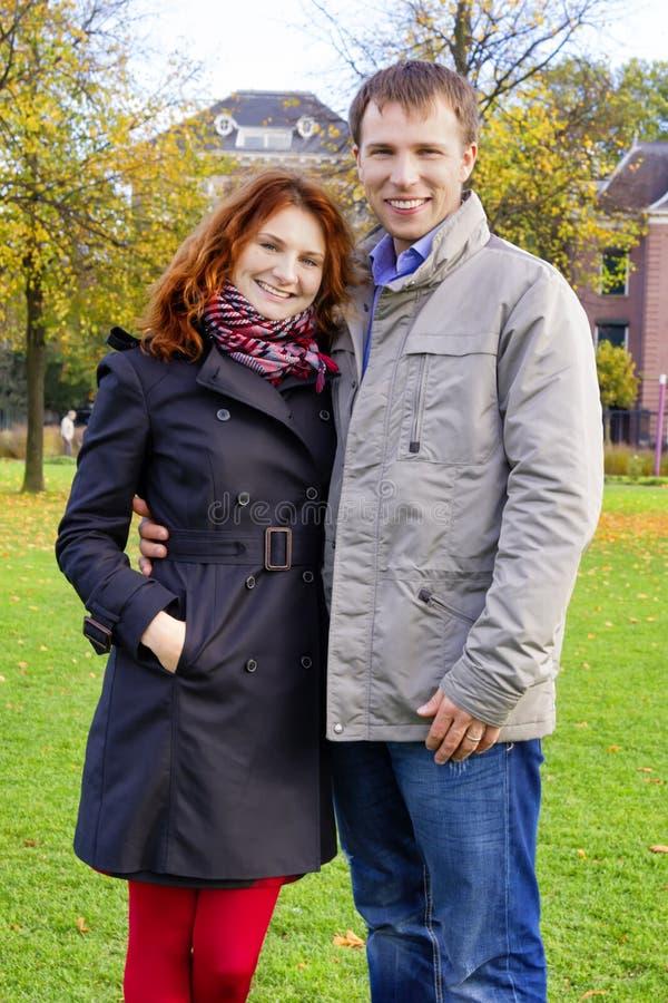 Glückliches Paar im Freien in der Liebe, die gegen Herbst Amsterdam aufwirft lizenzfreie stockbilder