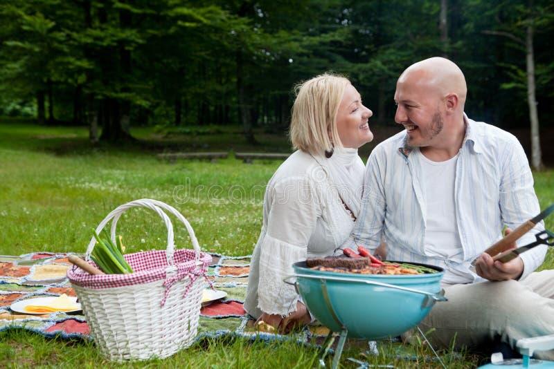 Glückliches Paar im Park mit Grill lizenzfreie stockfotografie