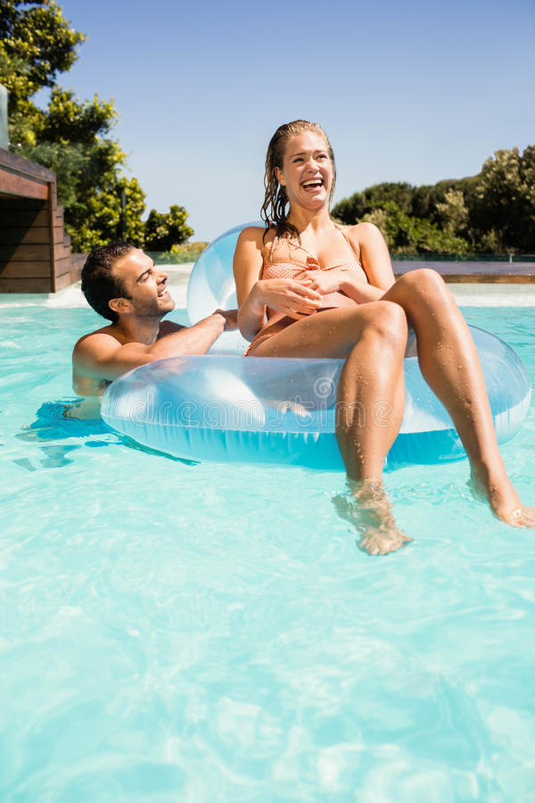 Glückliches Paar im Pool mit lilo stockfotos