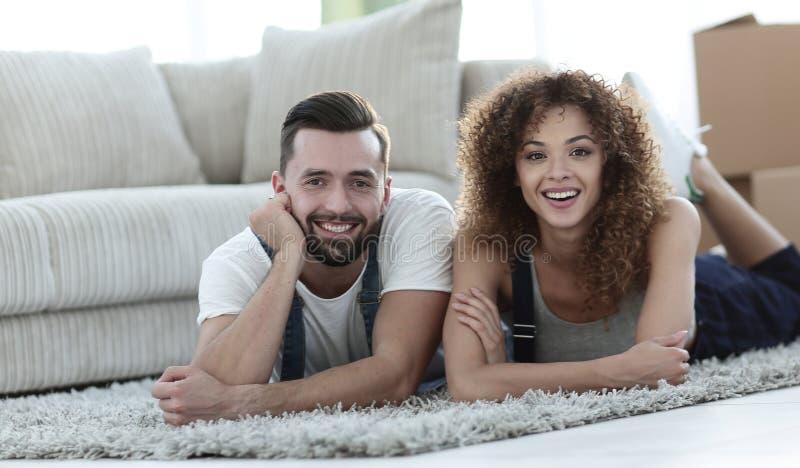 Glückliches Paar liegt auf dem Boden in einer neuen Wohnung lizenzfreies stockfoto
